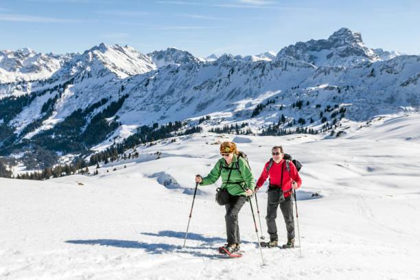 couple de personnes âgées est la randonnée en raquettes dans la montagne alpine hivernale. bavière, allemagne. - raquette photos et images de collection