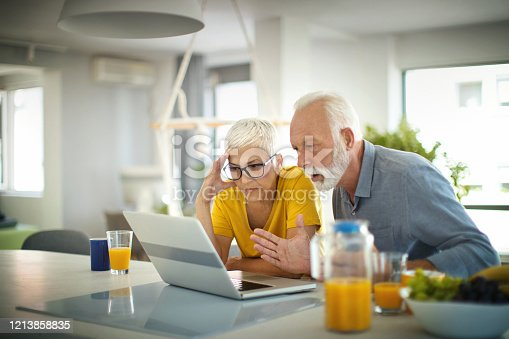 Closeup of a healthy senior couple staying at home and reading bad news about the ongoing spread of coronavirus. They are staying at home 24/7.  #stayathome #selfisolation  #socialdistancing  #flattenthecurve
