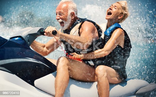 Closeup side view of a senior couple riding a jet ski on a sunny summer day at open sea. The man is driving quickly through the waves, and the lady is hardly holding on. Caught in the moment of max speed.