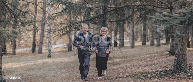 istock Senior couple jogging in a forest 1097398510