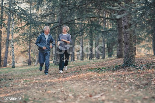 istock Senior couple jogging in a forest 1097399428