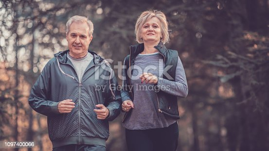 istock Senior couple jogging in a forest 1097400066