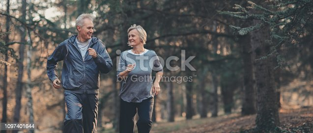 istock Senior couple jogging in a forest 1097401644