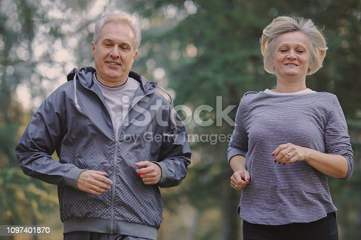 istock Senior couple jogging in a forest 1097401870
