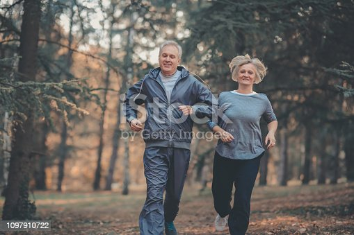 istock Senior couple jogging in a forest 1097910722