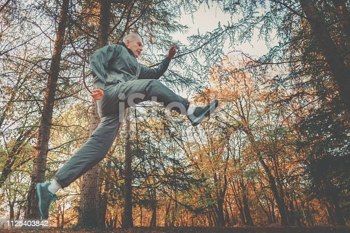 905501696 istock photo Senior couple jogging in a forest 1125403842