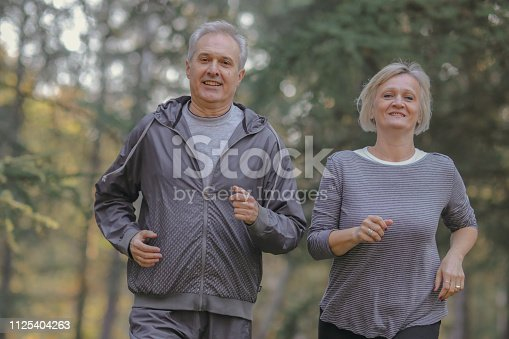 istock Senior couple jogging in a forest 1125404263