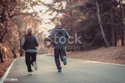 istock Senior couple jogging in a forest 1127128845