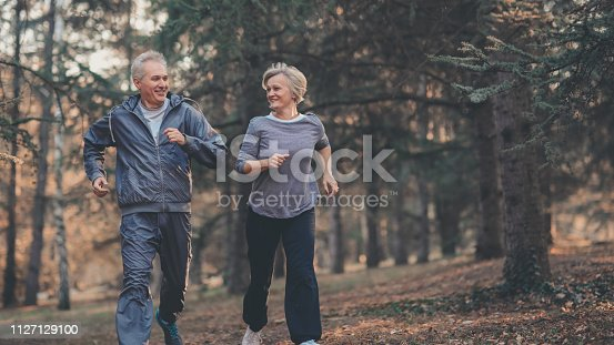 istock Senior couple jogging in a forest 1127129100