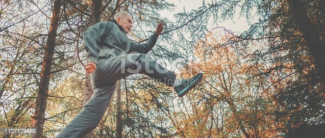 istock Senior couple jogging in a forest 1127129485