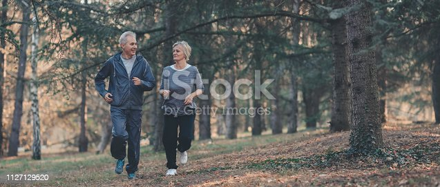 istock Senior couple jogging in a forest 1127129520