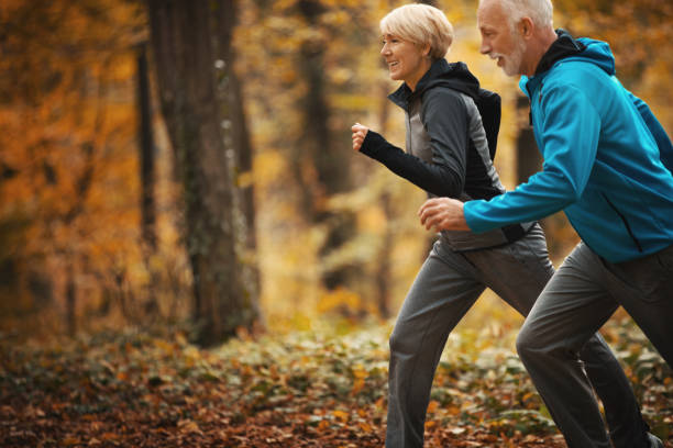 Senior-Paar joggen in einem Wald. – Foto
