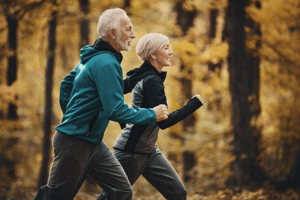 Senior couple jogging in a forest. stock photo