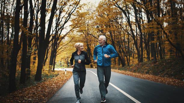 senior paar joggen in een forest. - groothoek stockfoto's en -beelden