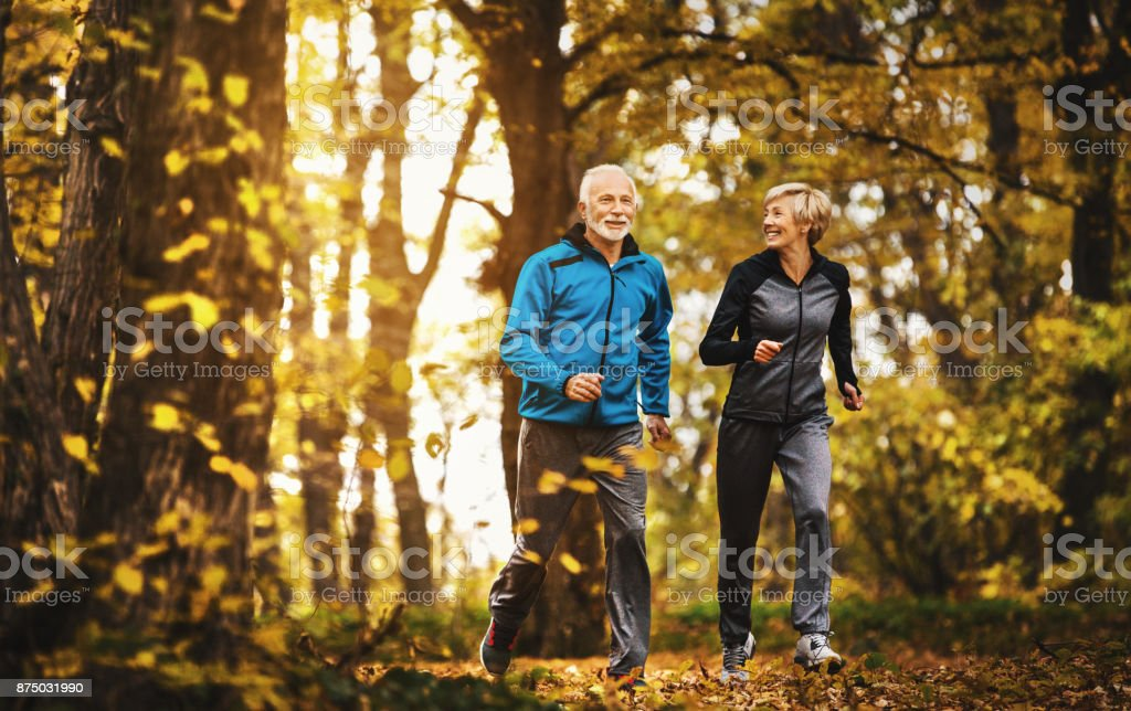 Älteres Paar im Wald joggen. – Foto