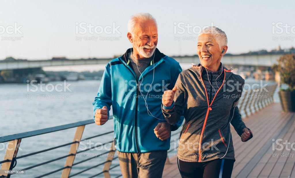Senior couple jogging Senior couple in sports clothing jogging together 50-59 Years Stock Photo