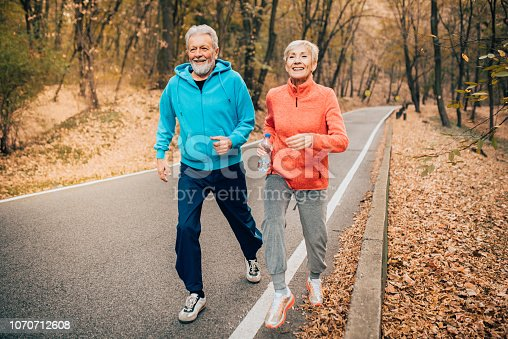 Fit senior couple jogging uphill in the autumn leaves covered park