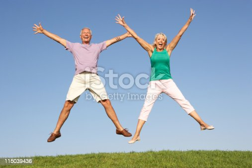 Senior couple jumping in air outside