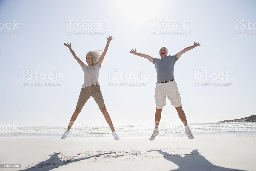 Senior couple jumping on beach stock photo