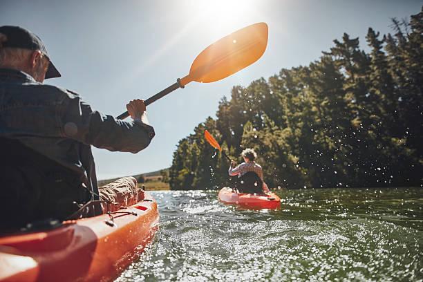 sênior casal andando de caiaque em um lago - esporte aquático - fotografias e filmes do acervo