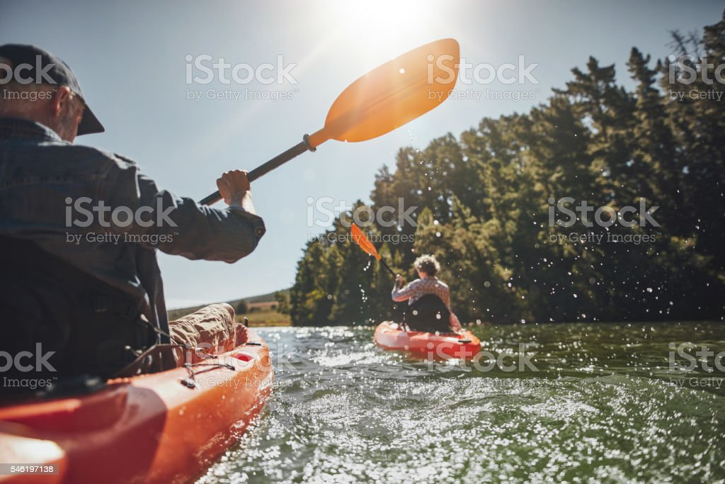 Senior couple kayaking in a lake stock photo