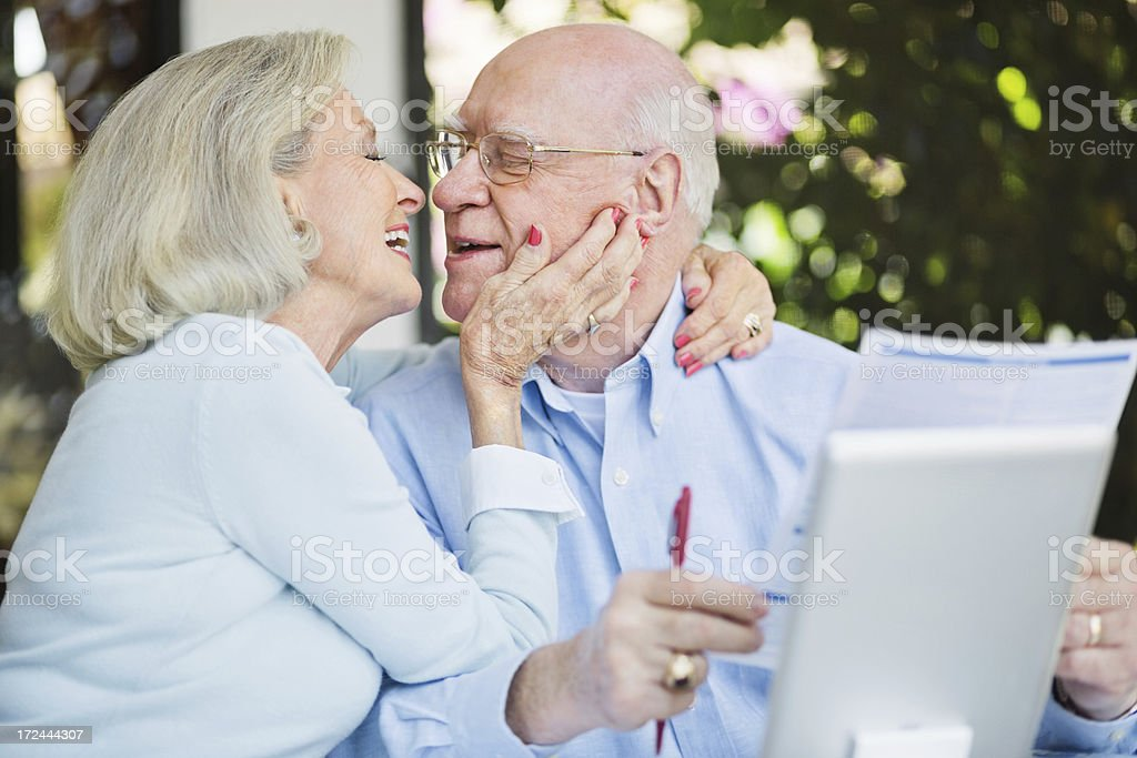 Senior Couple Kissing While Calculating Home Finance royalty-free stock photo