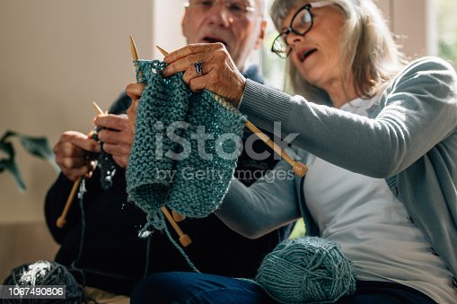 Senior woman teaching her husband the art of knitting woollen clothes. Senior man learning to knit woollen clothes from his wife sitting at home.