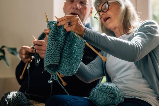 senior couple knitting wool at home - lavorare a maglia foto e immagini stock