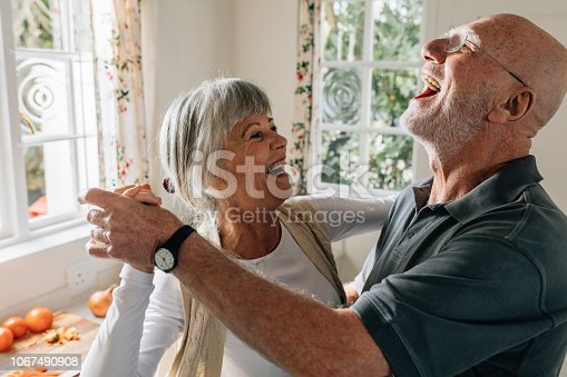 Senior man and woman dancing in joy at home. Happy senior couple having fun doing a ballroom dance at home.