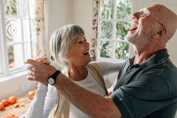 Senior couple laughing and having fun dancing Senior man and woman dancing in joy at home. Happy senior couple having fun doing a ballroom dance at home. dancing stock pictures, royalty-free photos & images
