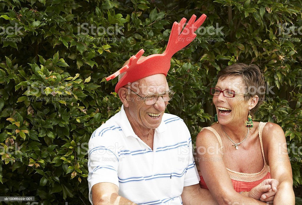 Senior couple laughing in yard, man wearing reindeer antlers royalty free stockfoto
