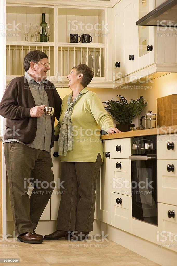 Altes Paar lachen zusammen in der Küche Lizenzfreies stock-foto