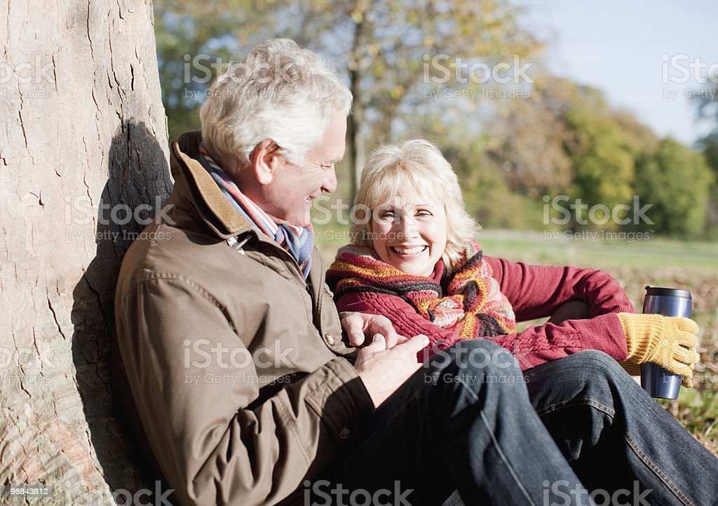 Senior couple leaning against tree trunk royalty free stockfoto