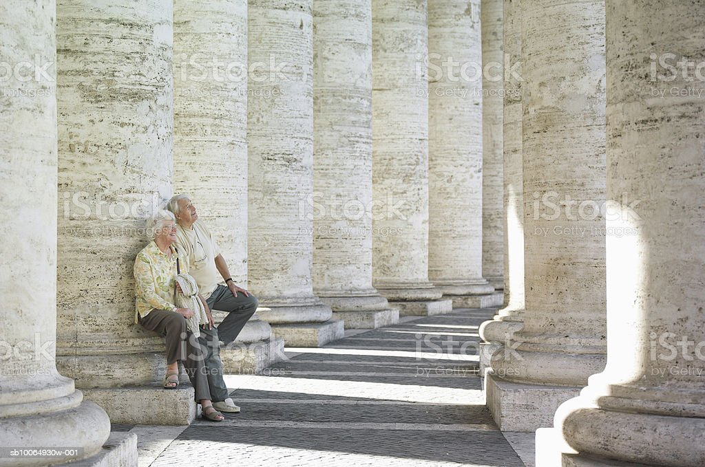 Senior couple leaning on columns, looking up royalty-free stock photo
