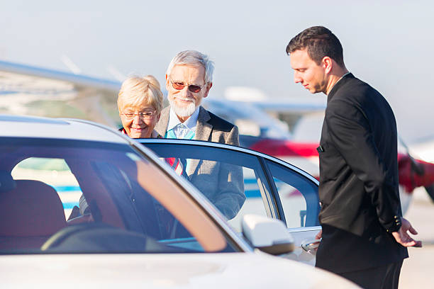 senior couple leaving airport in chauffeured car - limousine service stock photos and pictures
