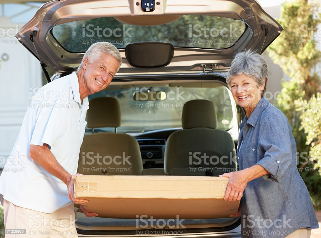 Senior Couple Loading Large Package Into Back Of Car stock photo