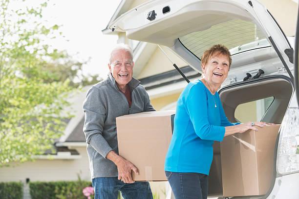 seniorenpaar be- und entladen von kisten von auto-kofferraum - stellenabbau stock-fotos und bilder