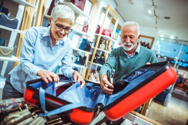 älteres paar blick auf einem roten koffer im ladengeschäft taschen und portemonnaies - trolley kaufen stock-fotos und bilder