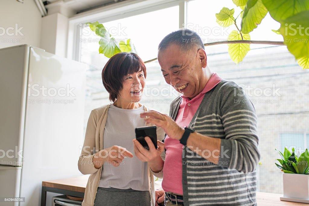 Senior couple looking at a smartphone laughing Senior couple looking at a smartphone together smiling. Kyoto, Japan. May 2016 Active Lifestyle Stock Photo