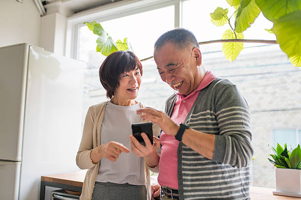 Senior couple looking at a smartphone laughing stock photo