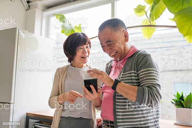 Senior Couple Looking At A Smartphone Laughing Stock Photo - Download Image Now