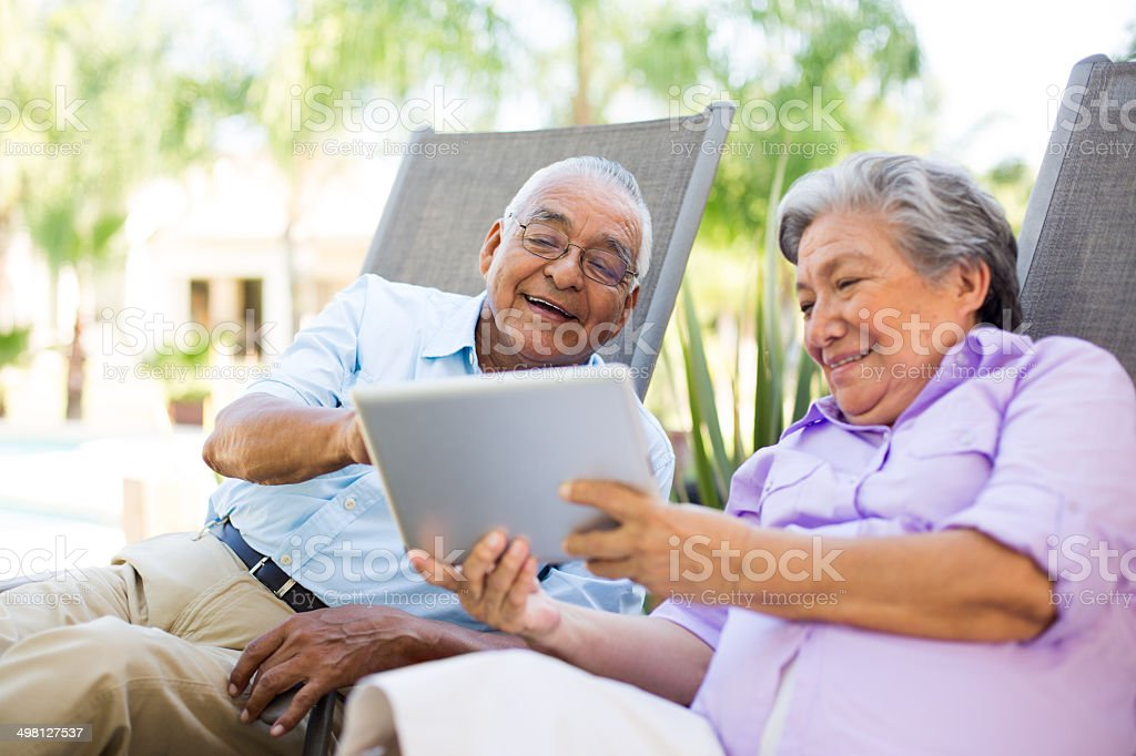 Senior couple looking at a tablet stock photo