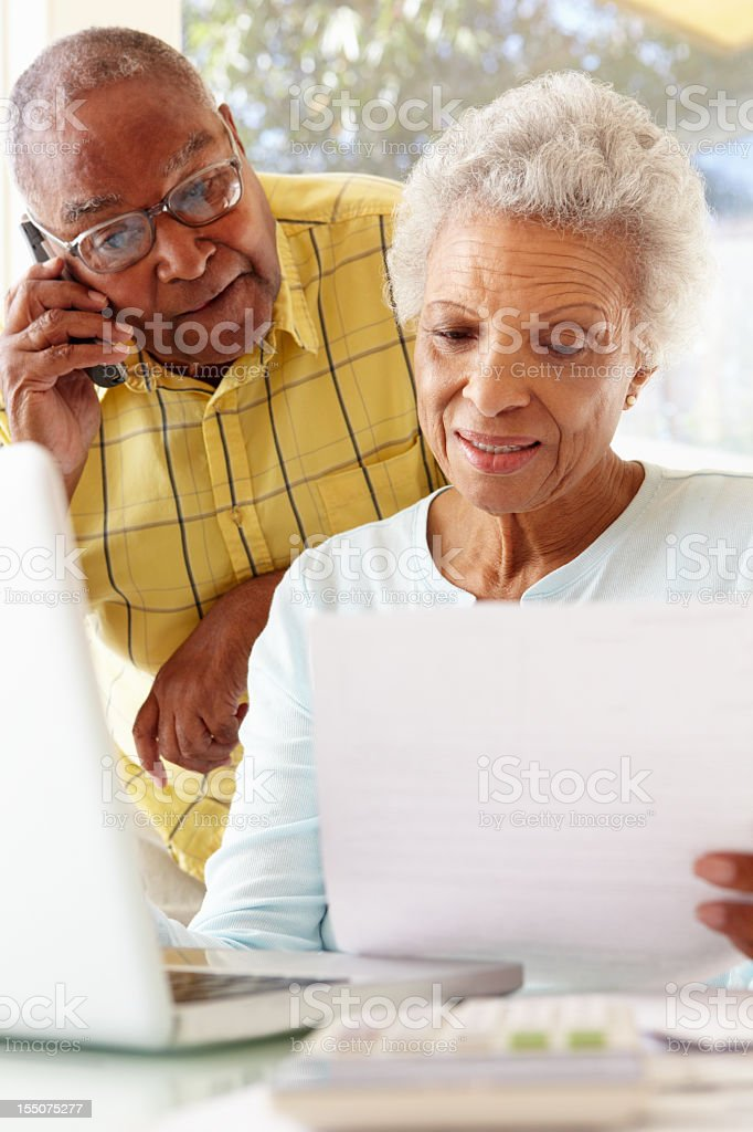 Senior couple looking at bills and using laptop stock photo