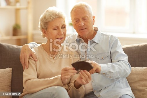 Portrait of modern senior couple looking  at photographs sitting on sofa at home lit by sunlight, copy space