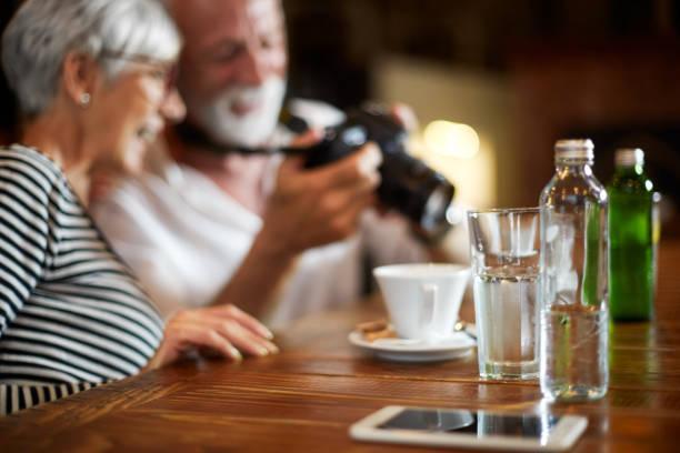älteres paar auf eine digitale kamera zusammen sitzen in einem café mit blick auf einige fotos - senior bilder wasser stock-fotos und bilder