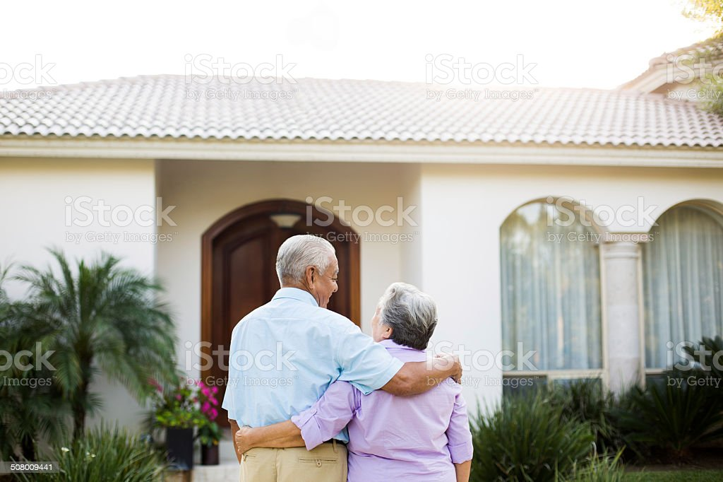 Senior couple looking at their house stock photo