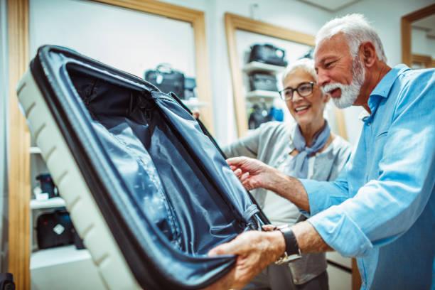 älteres paar auf der suche in einem weißen koffer im ladengeschäft taschen und portemonnaies - trolley kaufen stock-fotos und bilder