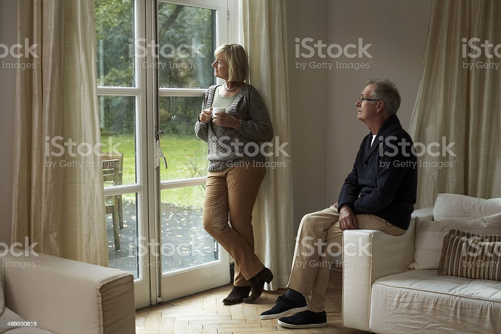Senior couple looking out through cottage door stock photo