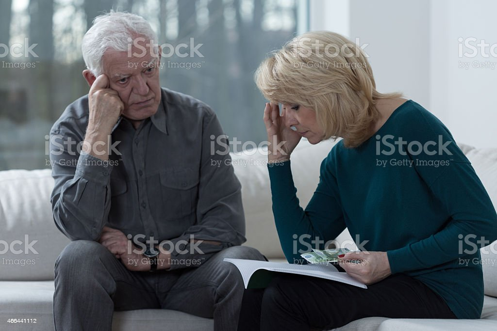 Senior couple looking troubled over papers stock photo