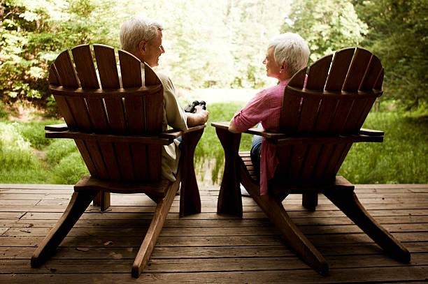 senior paar entspannung in den adirondack stühle auf einem holz-deck - verandas stock-fotos und bilder